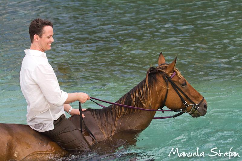 Groom riding horse in Jamaica
